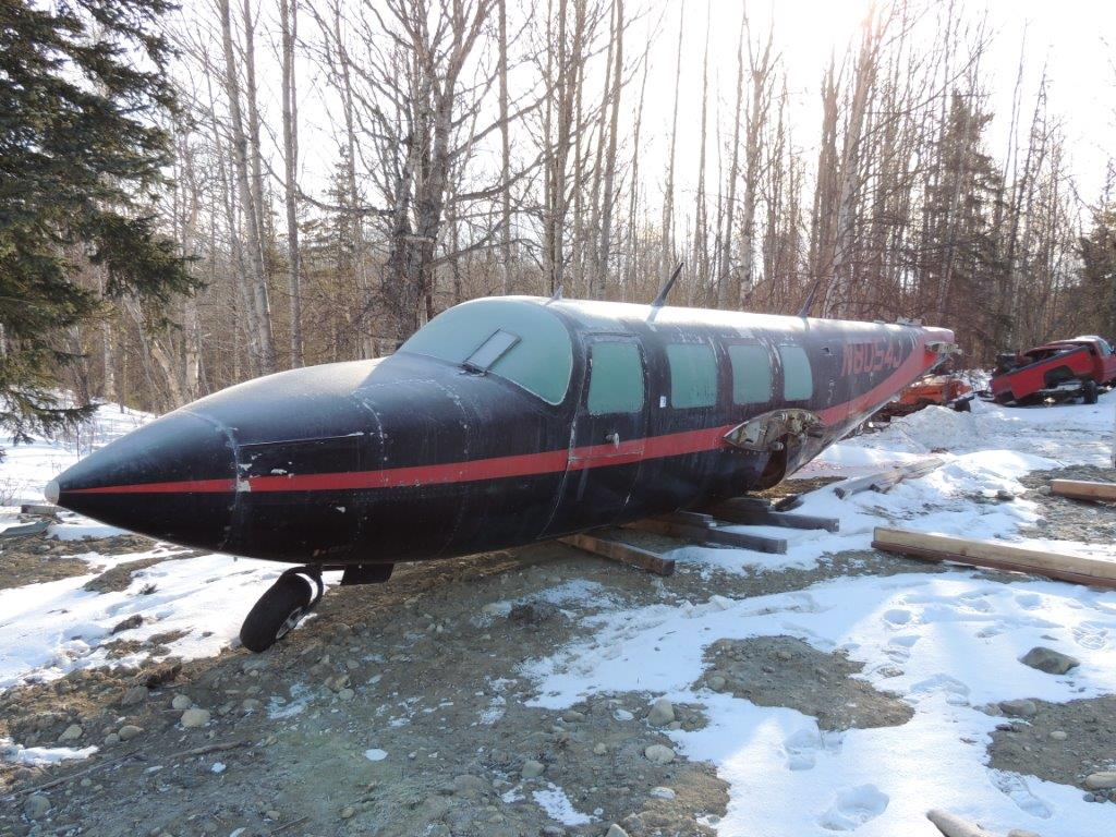 A black Piper Aerostar stills propped up on wooden posts among barren trees and snow ladden ground.